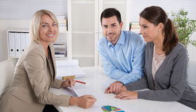 Professional business meeting: young couple as customers and an Stock Images