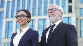 Professional business partners standing outdoor, experienced office workers stock image