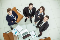 Professional business team looking up standing near desktop Royalty Free Stock Images
