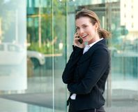 Professional business woman smiling with mobile phone outside. Side portrait of a professional business woman smiling with mobile phone outside Royalty Free Stock Images