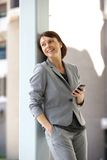 Professional business woman standing with mobile phone. Portrait of a professional business woman standing with mobile phone Royalty Free Stock Images