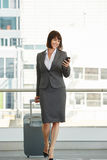 Professional business woman with suitcase and smart phone. Full length portrait of professional business woman with suitcase and smart phone Royalty Free Stock Images