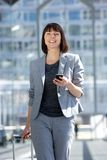 Professional business woman traveling with bag and mobile phone. Portrait of a professional business woman traveling with bag and mobile phone Royalty Free Stock Images
