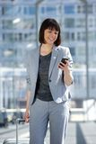 Professional business woman traveling. Portrait of a professional business woman traveling. Woman reading text message on mobile phone Stock Photos
