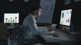 Professional businessman analyzing financial charts and data in night office stock footage