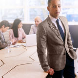 Professional businessman standing in front of his business colleagues indoors stock image