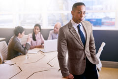 Professional businessman standing in front of his business colleagues indoors stock photos