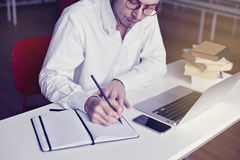 Professional businessmProfessional businessman working writing in office or library with. Professional businessman working writing in office or library with book Stock Photo