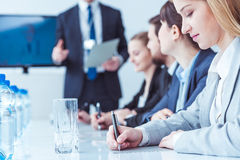 Professional businesswoman in corporation. Young pretty professional businesswoman in group of businesspeople during meeting in corporation Stock Photos