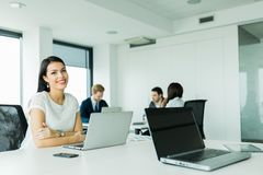 Professional businesswoman sitting at an office desk Stock Image