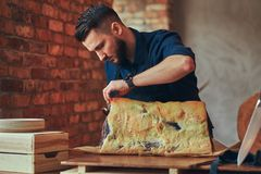 Professional butcher is cutting raw smoked meat on a table for c. Professional butcher is cutting raw smoked meat on a table royalty free stock photo