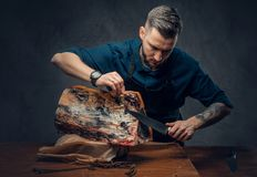 Professional butcher is cutting raw smoked meat on a table for c. Professional butcher with raw smoked meat in a studio stock photography