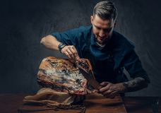Professional butcher is cutting raw smoked meat on a table for c. Professional butcher with raw smoked meat in a studio stock photos