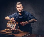 Professional butcher is cutting raw smoked meat on a table for c. Professional butcher with raw smoked meat in a studio stock images
