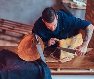 Professional butcher is cutting raw smoked meat on a table for c. Professional butcher is cutting raw smoked meat on a table royalty free stock images