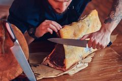 Professional butcher is cutting raw smoked meat on a table for c. Professional butcher is cutting raw smoked meat on a table royalty free stock photography