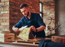 Professional butcher is cutting raw smoked meat on a table for c. Professional butcher is cutting raw smoked meat on a table royalty free stock image