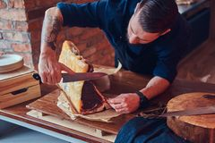 Professional butcher is cutting raw smoked meat on a table for c. Professional butcher is cutting raw smoked meat on a table stock image