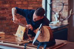 Professional butcher is cutting raw smoked meat on a table for c. Professional butcher is cutting raw smoked meat on a table stock images