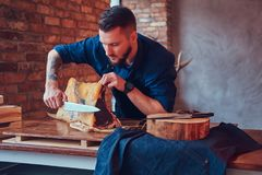 Professional butcher is cutting raw smoked meat on a table for c. Professional butcher is cutting raw smoked meat on a table stock photography