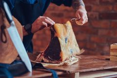 Professional butcher is cutting raw smoked meat on a table for c. Professional butcher is cutting raw smoked meat on a table Royalty Free Stock Photos