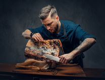 Professional butcher is cutting raw smoked meat on a table for c. Professional butcher with raw smoked meat in a studio royalty free stock image