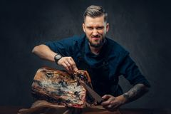 Professional butcher is cutting raw smoked meat on a table for c. Professional butcher with raw smoked meat in a studio royalty free stock photo