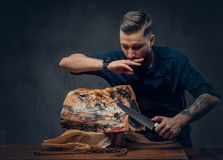 Professional butcher is cutting raw smoked meat on a table for c. Professional butcher with raw smoked meat in a studio royalty free stock photography