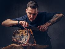 Professional butcher is cutting raw smoked meat on a table for c. Professional butcher with raw smoked meat in a studio stock photo