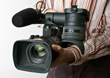 Professional camera. A man holding a professional video camera Stock Images
