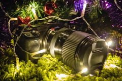 Professional camera as a gift for new year or Christmas. This camera cannot charge lies under the Christmas tree in the bright lights Stock Photography