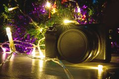 Professional camera as a gift for new year or Christmas. This camera cannot charge lies under the Christmas tree in the bright lights Stock Photo