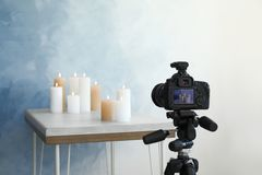 Professional camera and candles on table. Against color wall stock photos
