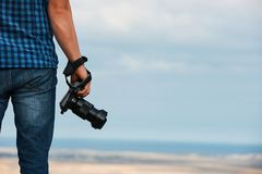 Professional camera in man`s hand. Photosession on a background of ocean landscape, copy space stock photos