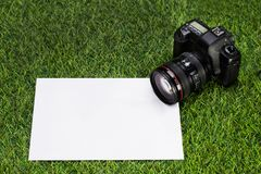 Professional camera with sheet of paper lying on the grass Stock Photo