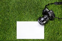 Professional camera with sheet of paper lying on the grass Royalty Free Stock Photo