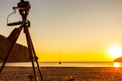 Camera taking picture of sunrise over sea surface Stock Images