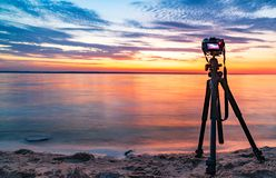 Professional camera taking picture film video of sunrise over sea surface Stock Images