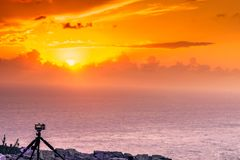 Camera taking picture film of sunset over sea surface Royalty Free Stock Image