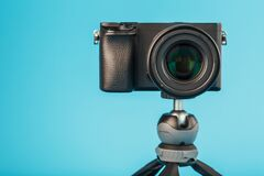 Professional camera on a tripod, on a blue background. Record videos and photos for your blog or report