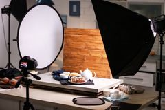 Professional camera on tripod and food composition. In photo studio royalty free stock images