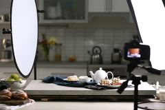 Professional camera on tripod and food composition. In photo studio royalty free stock image