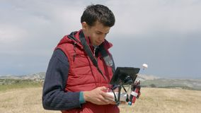 Professional cameraman controlling drone flight, watching display, filming video stock footage
