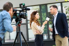 Professional cameraman and journalist interviewing businessman near office. Building stock photos