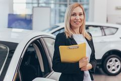 Saleswoman working at car dealership. Professional car dealer posing proudly at auto showroom, smiling to the camera, holding clipboard. Happy saleswoman working royalty free stock images