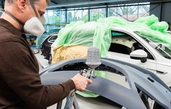 Professional car varnisher at work in a service station - Serie car repair workshop. Professional car lacquer at work in a service station - Serie car repair royalty free stock images