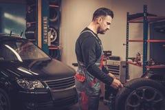 Professional car mechanic balancing car wheel on balancer in au. To repair service stock images