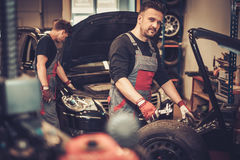 Professional car  mechanic balancing car wheel on balancer in au Royalty Free Stock Image