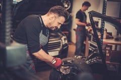 Professional car mechanic balancing car wheel on balancer in auto repair service. stock photo