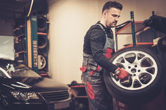Professional car mechanic balancing car wheel on balancer in auto repair service. Royalty Free Stock Images
